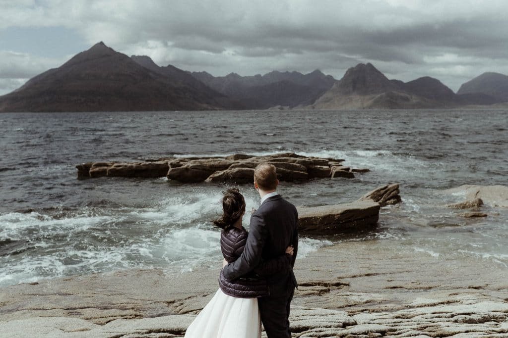 elgol-elopement-couple-looking-out-to-cuillin-mountains-on-the-sea-shore