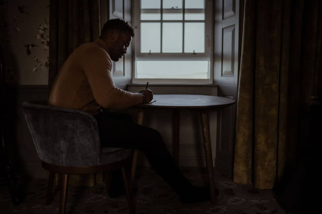 Groom writing his  elopement ceremony vows at a table by the window