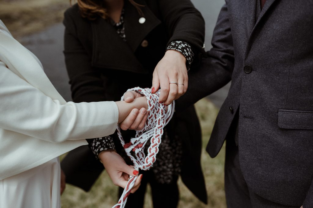 bride and groom having their hands tied in a hand-fasting ceremony by their celebrant