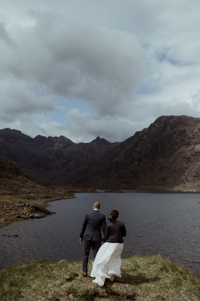 Couple walking by a loch surrounded by the Cuillin Mountains on the Isle of Skye